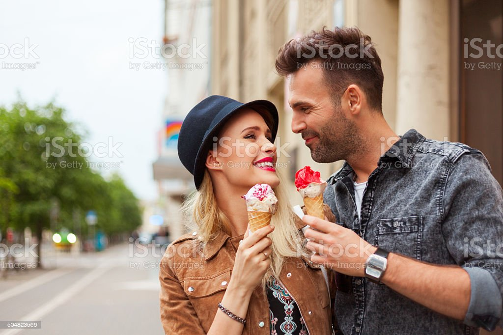 Affectionate couple eating ice cream in the city stock photo