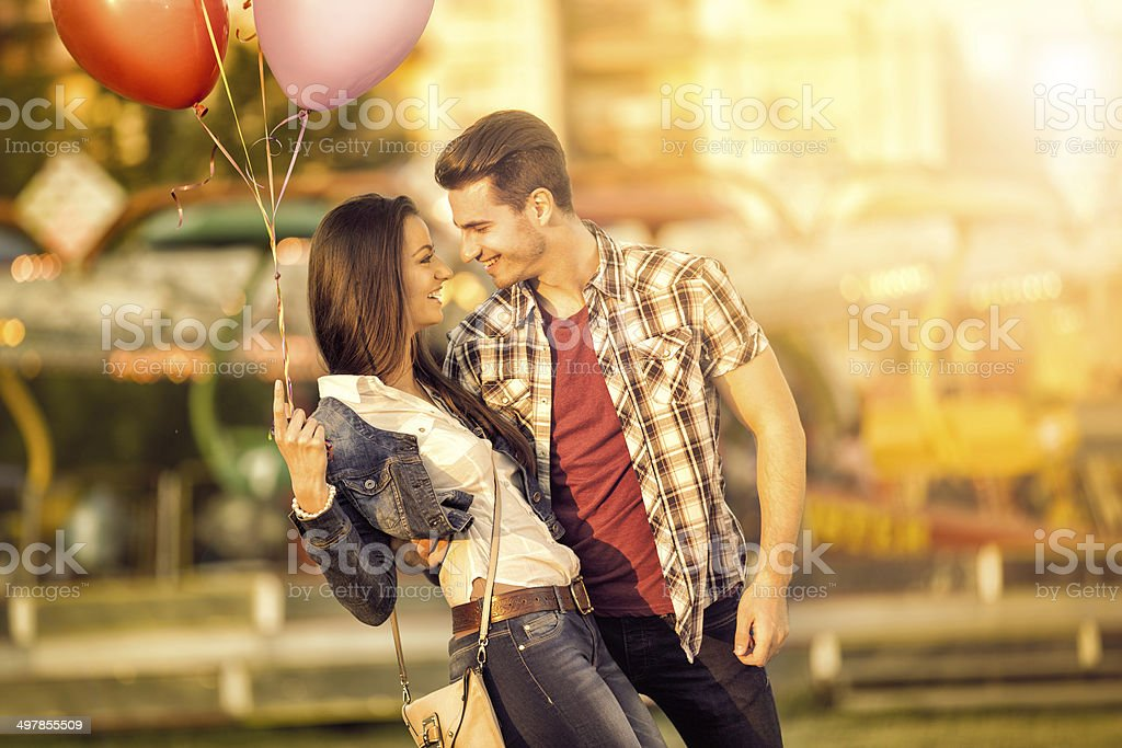 Affectionate couple having fun in amusement park stock photo