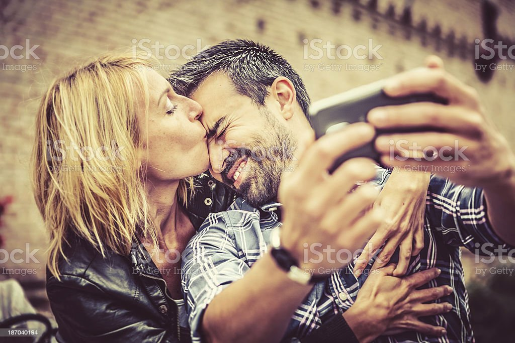 Affectionate Couple Having Fun with Smartphone royalty-free stock photo