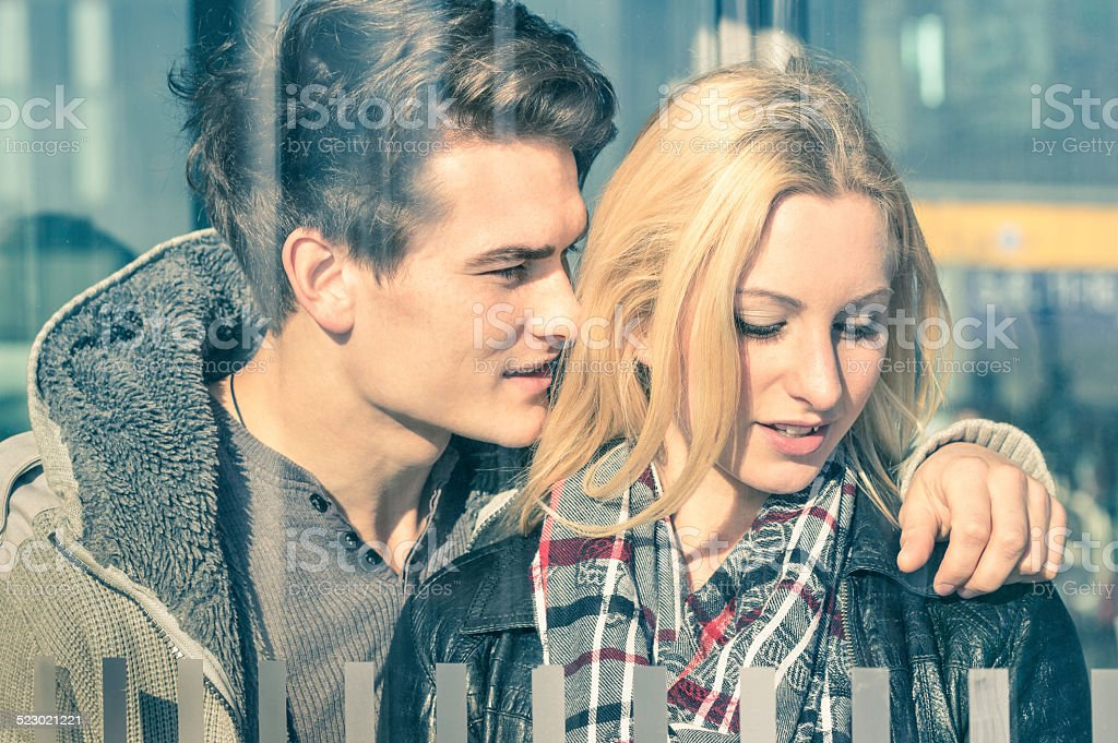 Affectionate couple in love behind glass reflections stock photo