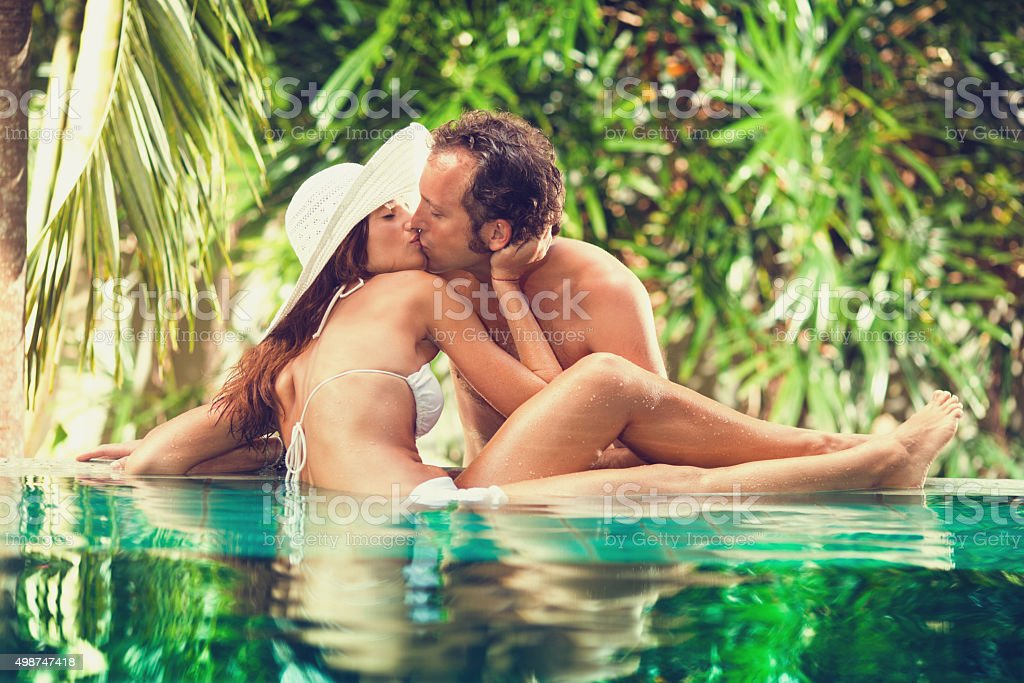 Affectionate couple kissing in swimming pool. stock photo