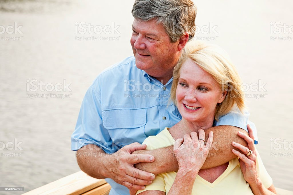 Affectionate couple relaxing by water stock photo