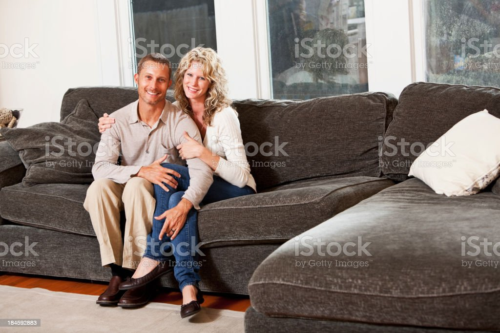 Affectionate couple sitting on couch stock photo