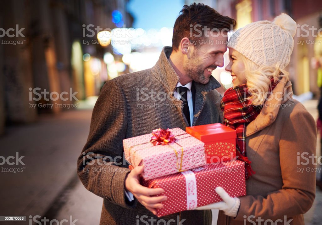 Affectionate couple with stack of presents stock photo