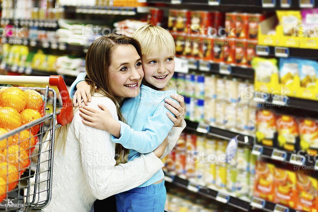 Affectionate embrace between mother and daughter in supermarket royalty-free stock photo