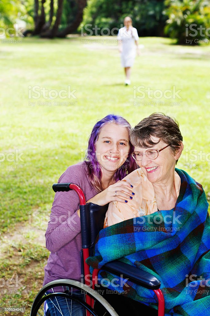 Affectionate family moment between grandmother and granddaughter; caregiver loking on stock photo