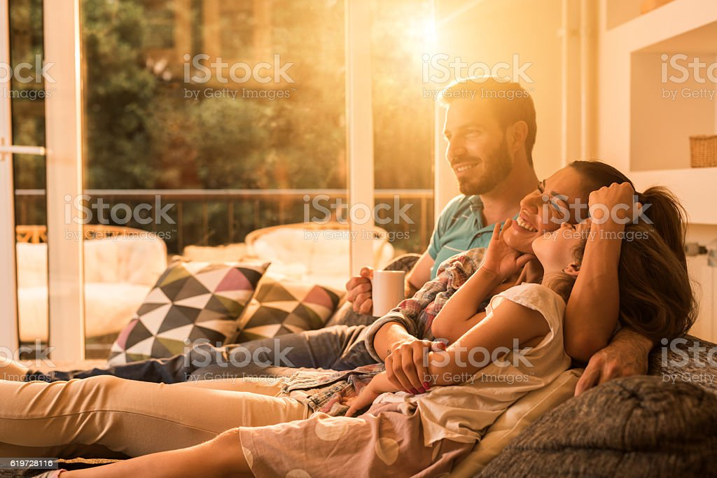 Affectionate family relaxing together in the living room. stock photo