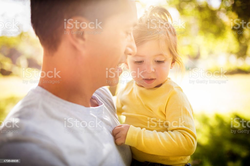 Affectionate father carrying his little girl lovingly stock photo