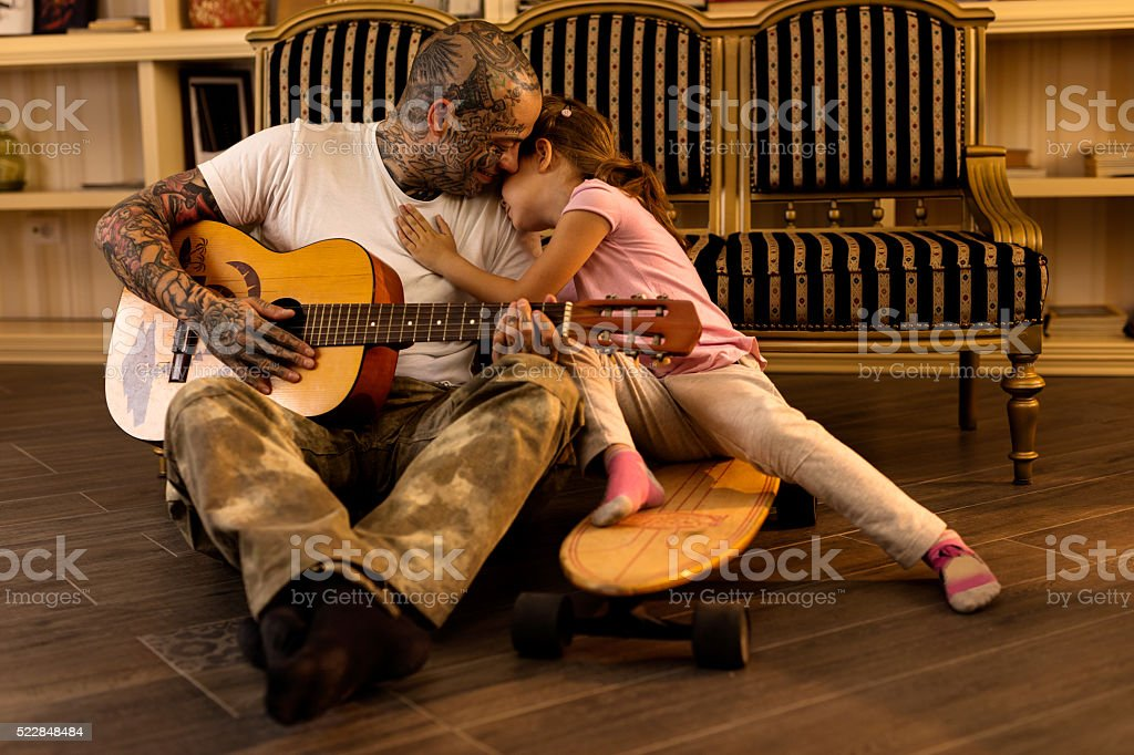 Affectionate father playing acoustic guitar to his little girl. stock photo