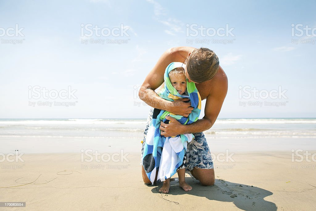 Affectionate father wrapps his son in a towel stock photo