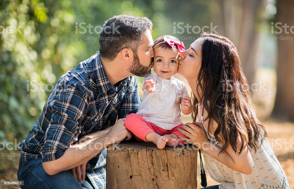 Affectionate latin parents kissing baby daughter on cheeks stock photo