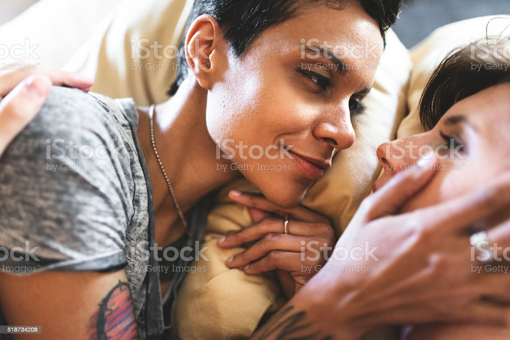 affectionate lesbian couple on the bed stock photo