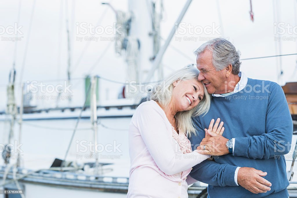 Affectionate mature couple at marina stock photo