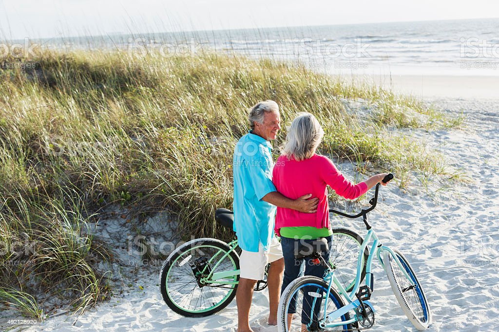 Affectionate mature couple with bikes at beach stock photo