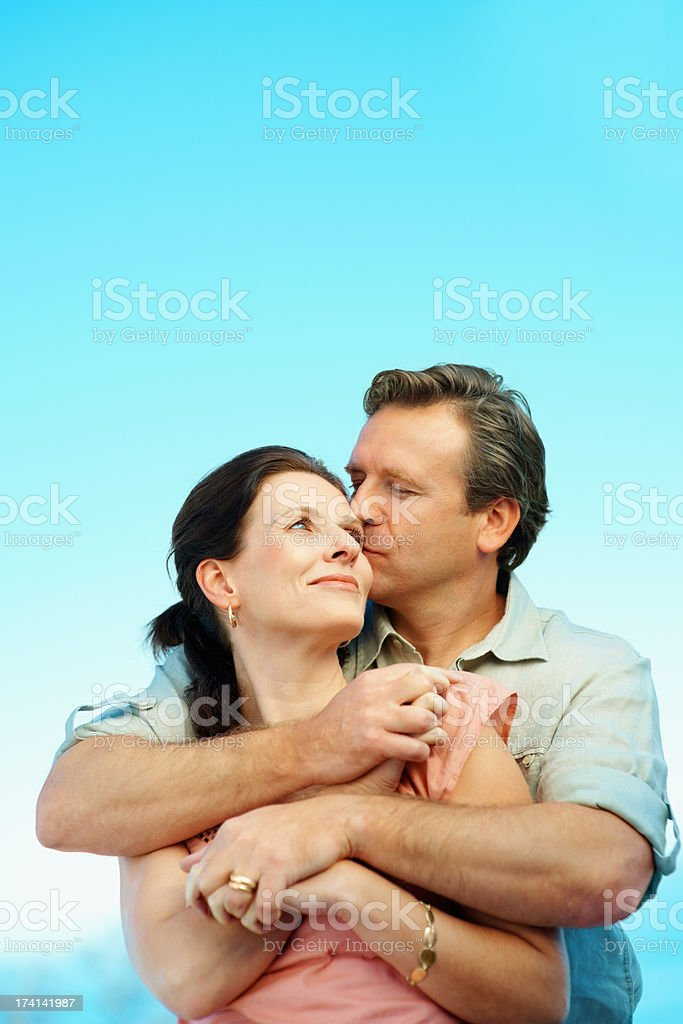 Affectionate mature man giving a hug to a cute woman stock photo