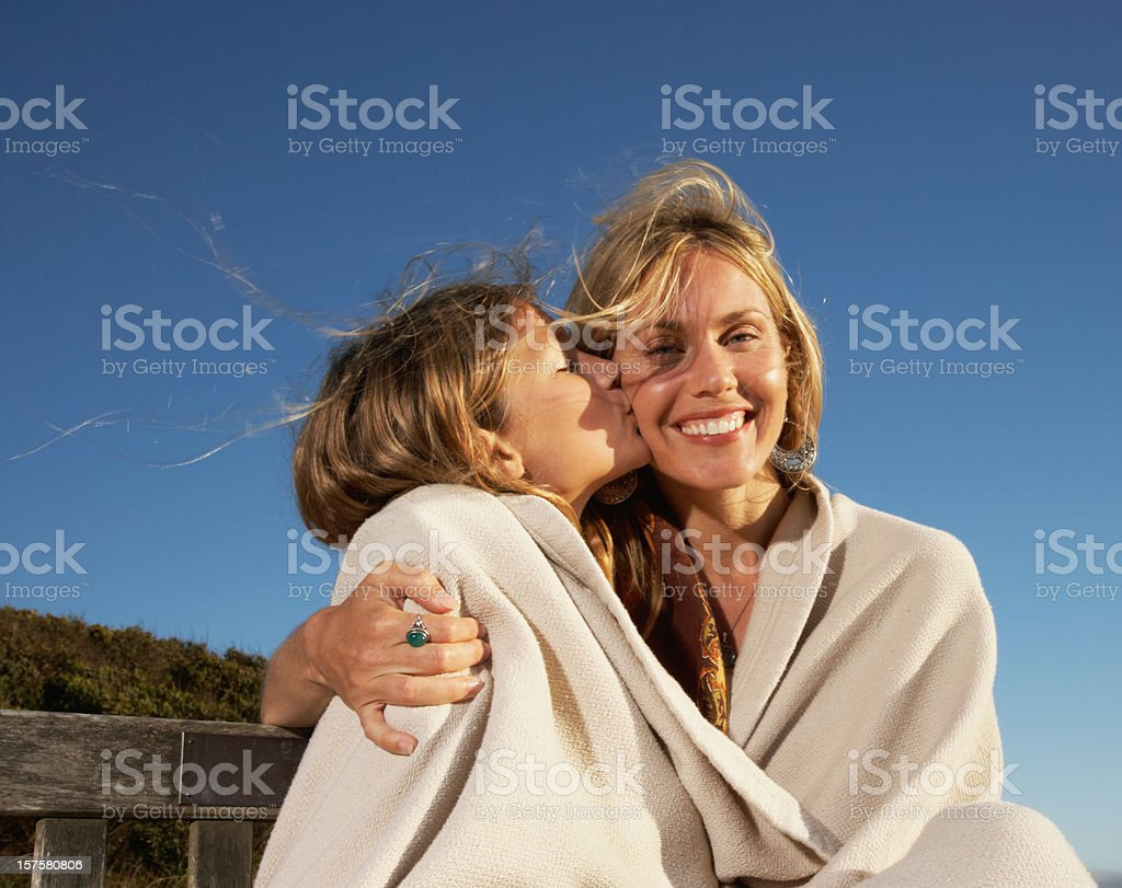 Affectionate Mom and Teen Daughter Wrapped in Blanket royalty-free stock photo