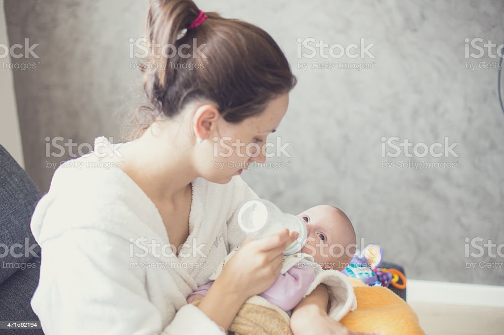 Affectionate mother feeding bottle to her baby stock photo