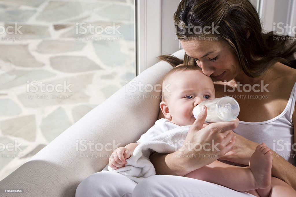 Affectionate mother feeding bottle to six month old baby stock photo