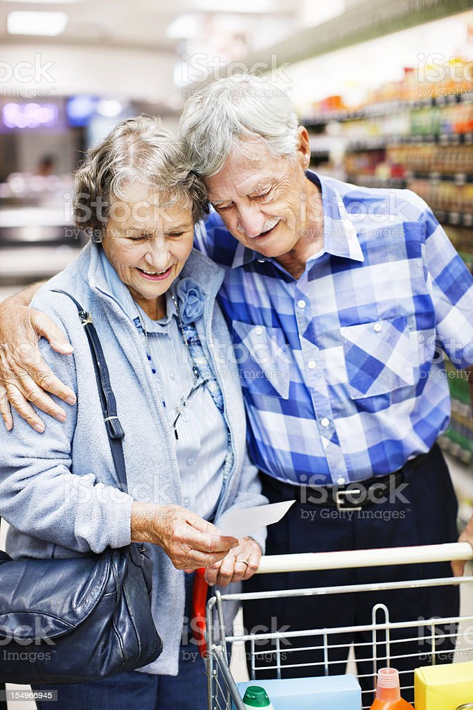 Affectionate senior couple check their shopping list in the supermarket stock photo