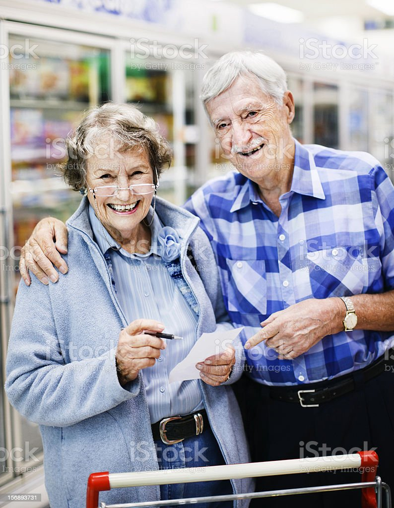 Affectionate senior couple checking list smile delightedly in supermarket stock photo