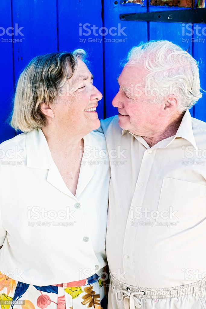 Affectionate senior couple embrace, smiling at each other stock photo