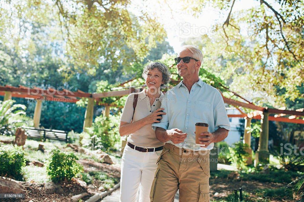 Affectionate senior couple enjoying a walk in the park stock photo