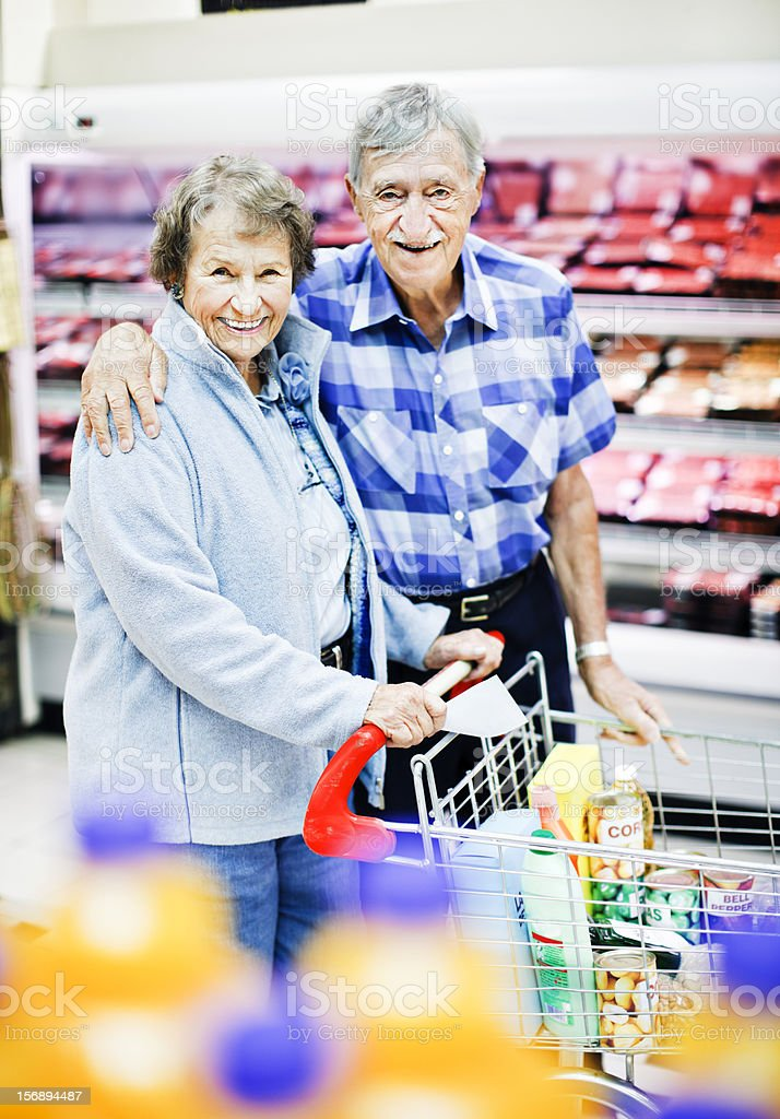 Affectionate senior couple smile happily for camera while supermarket shopping stock photo