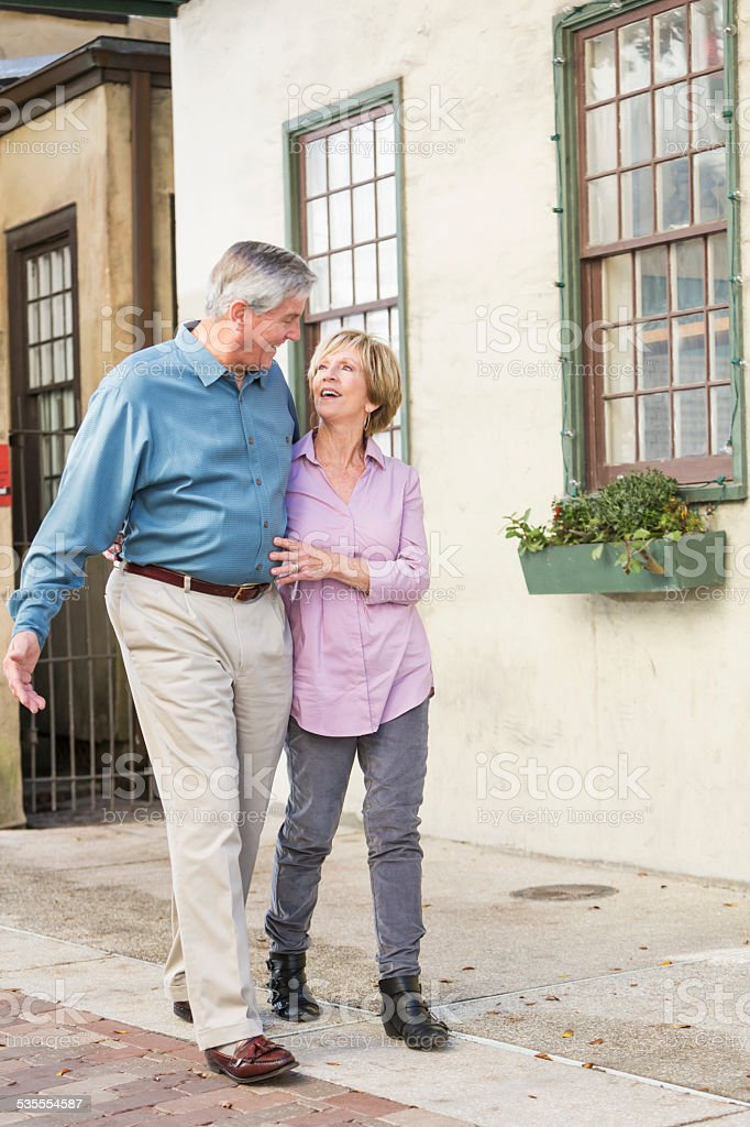 Affectionate senior couple taking a stroll stock photo
