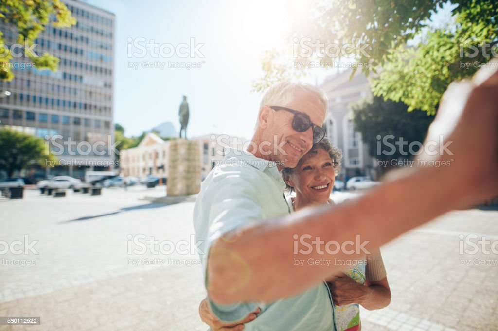Affectionate senior tourists taking a selfie outdoors stock photo