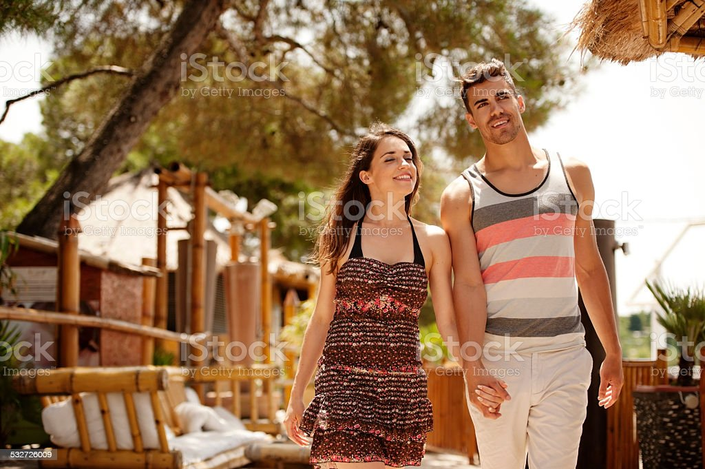Affectionate young couple walking in a outdoors bar stock photo