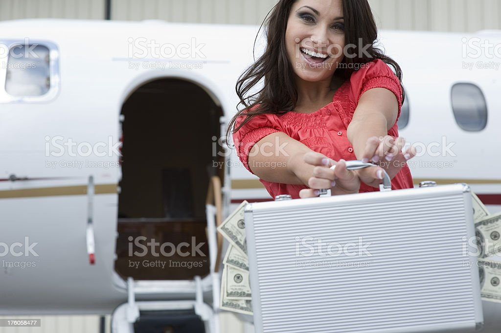 Affluent Travel - Beautiful woman with briefcase full of cash royalty-free stock photo
