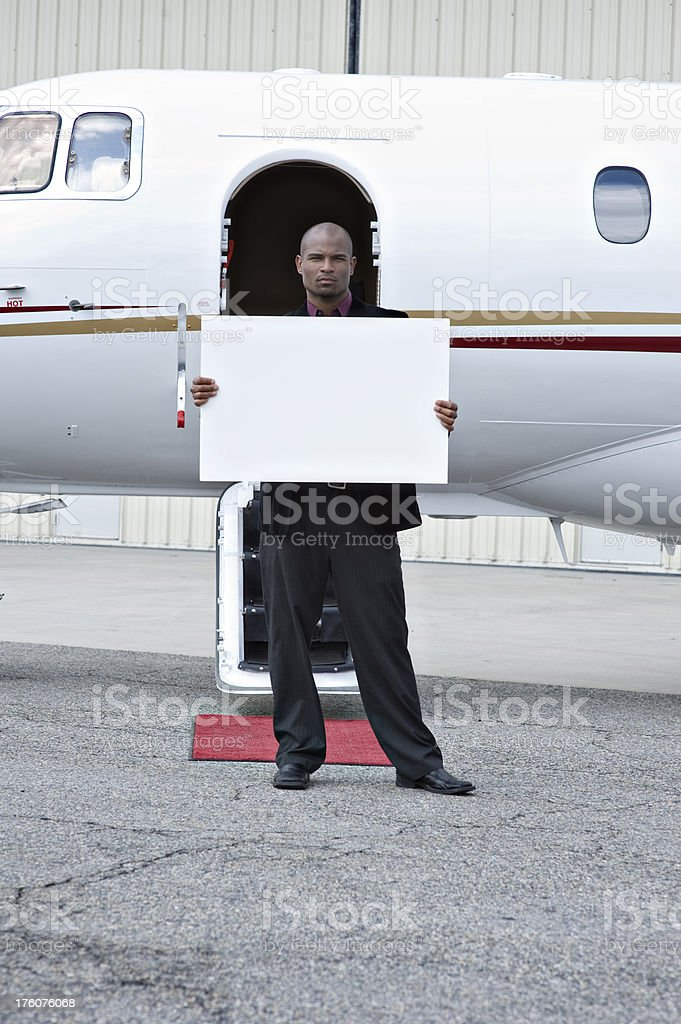Affluent Travel - Businessman with blank sign by private jet royalty-free stock photo