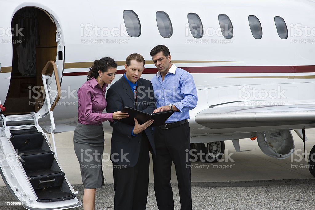 Affluent Travel - Three business people and a private jet royalty-free stock photo