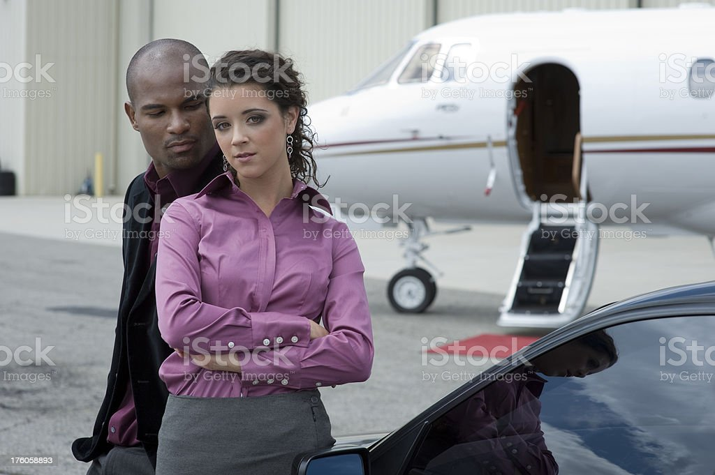 Affluent Travel - Wealthy man and woman with private jet royalty-free stock photo
