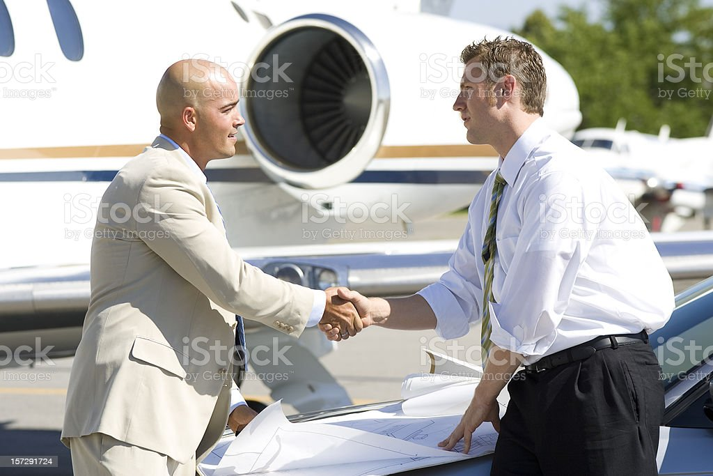 Affluent Travel-Businessmen Shaking Hands by Airplane royalty-free stock photo