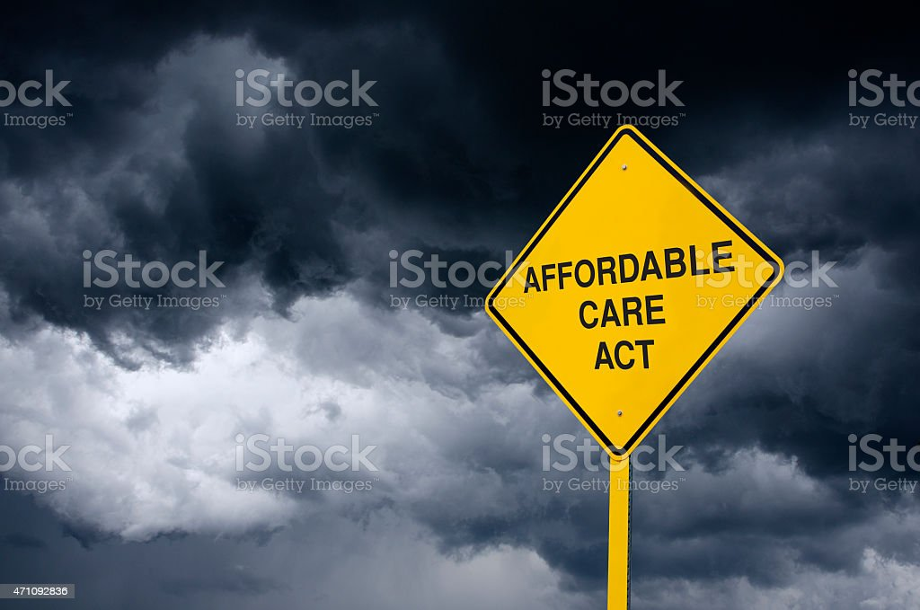 Affordable Care Act Road Sign in Front of Storm Clouds stock photo