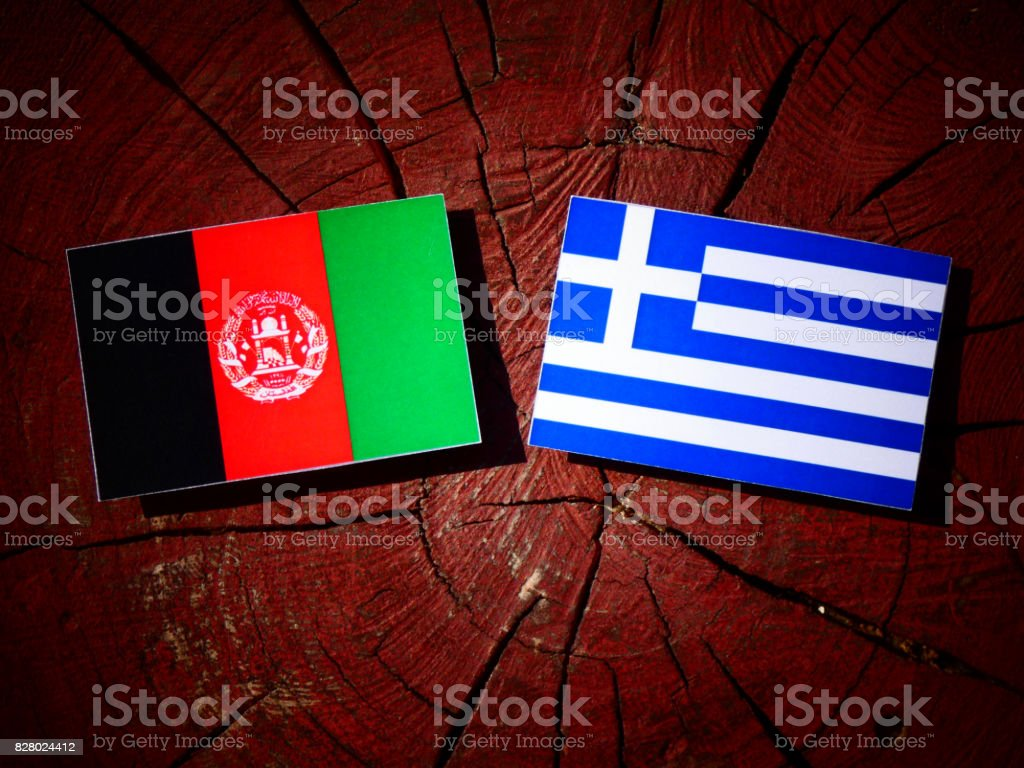 Afghanistan flag with Greek flag on a tree stump isolated stock photo