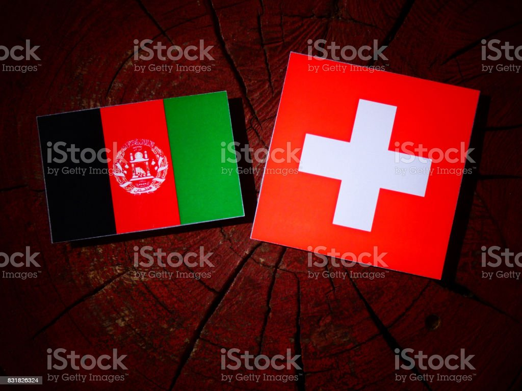 Afghanistan flag with Swiss flag on a tree stump isolated stock photo