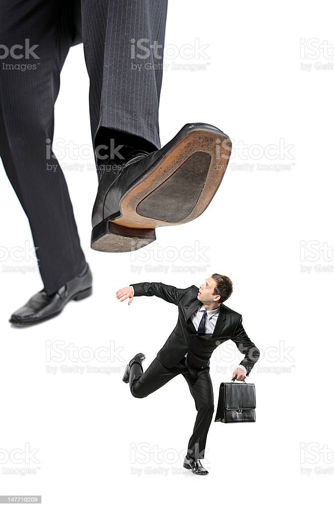 Afraid businessman running away from a big foot stock photo