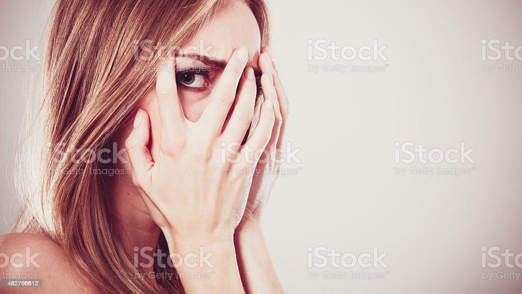 Afraid frightened woman peeking through her fingers stock photo