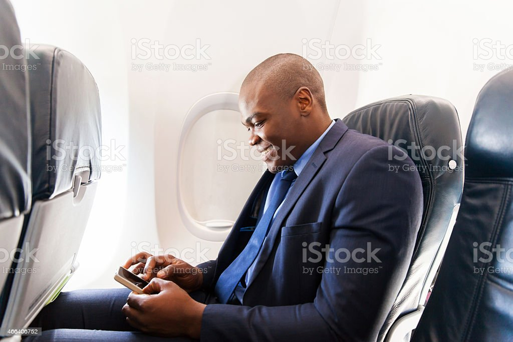 african airplane passenger using smart phone on plane stock photo