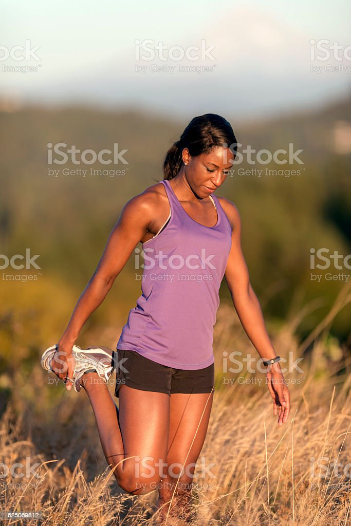 African American adult female athlete stretching leg before trail run stock photo
