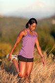 African American adult female athlete stretching leg before trail run
