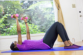 African American adult female using weights on a yoga mat