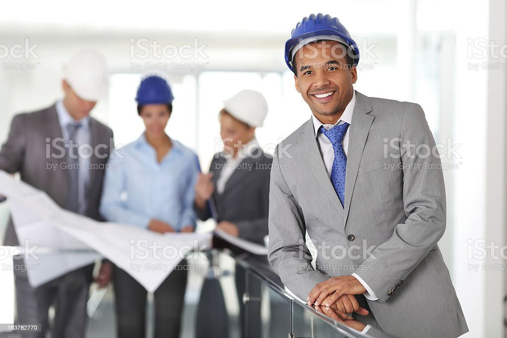 African American architect looking at camera in the foreground. royalty-free stock photo