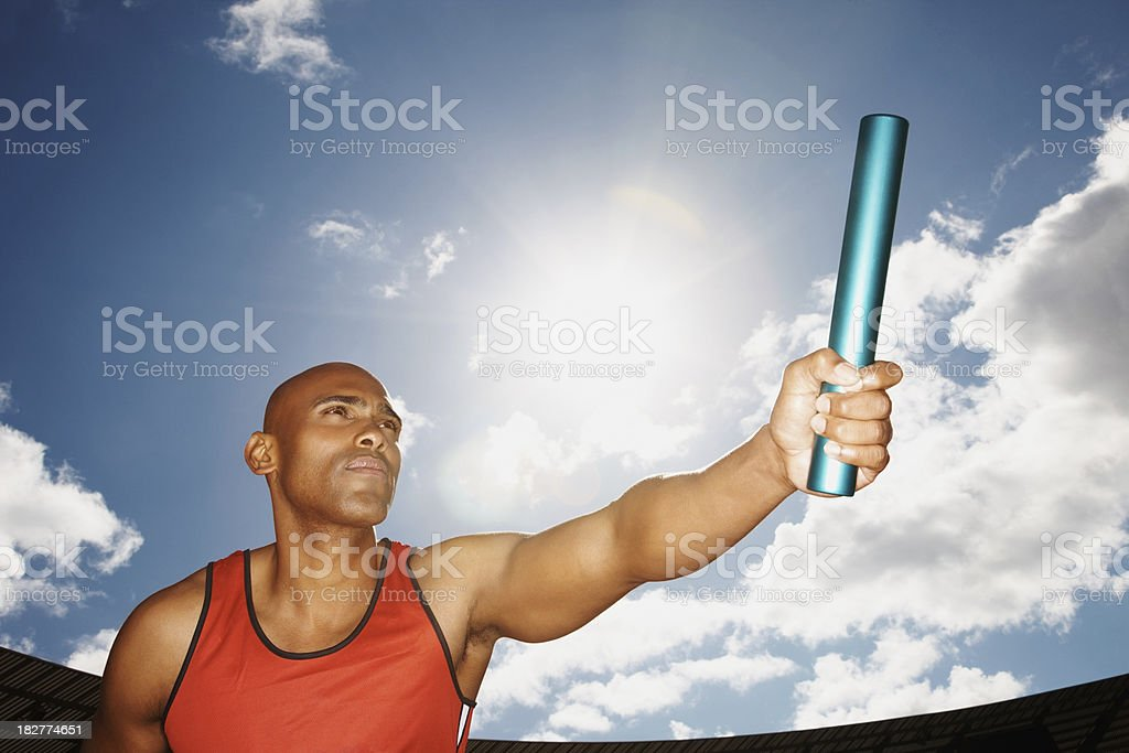 African American athlete holding a baton against sky royalty-free stock photo