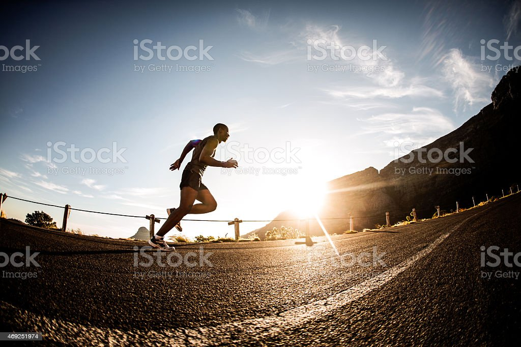 African American athlete running in the morning with bright sky stock photo