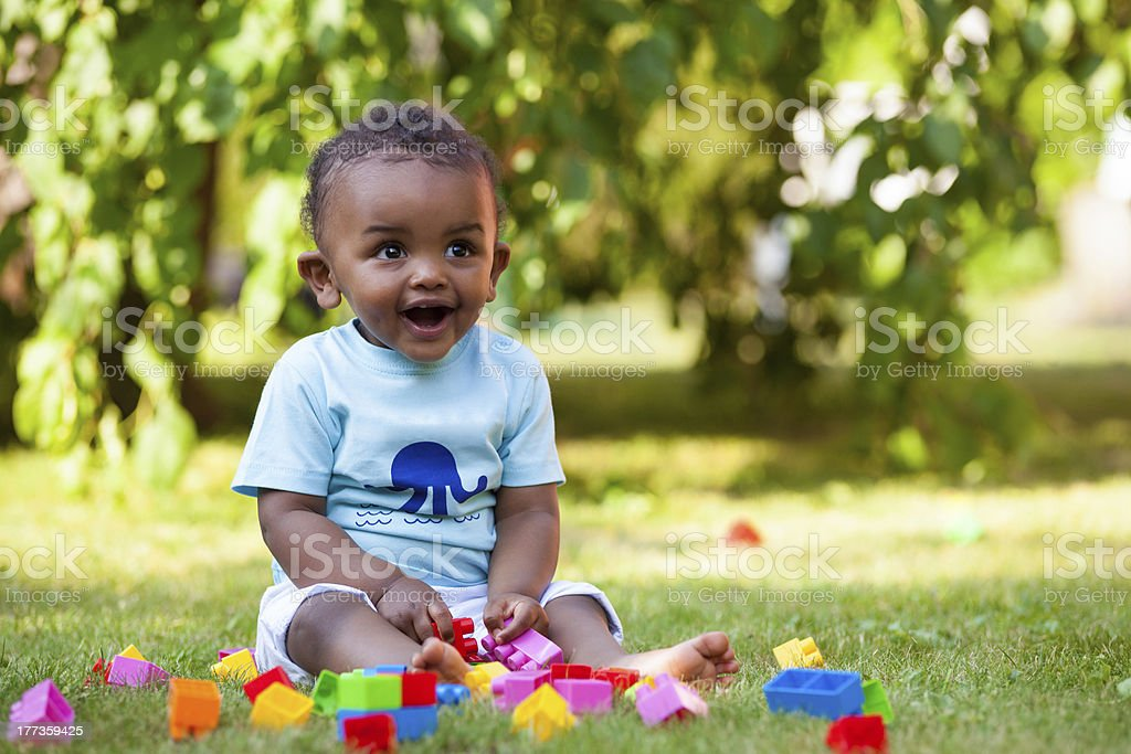 African american baby boy playing in the grass stock photo