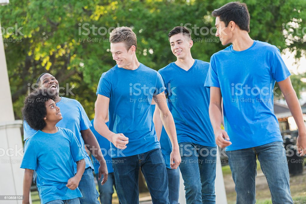 African American boy and group of teens in blue shirts stock photo