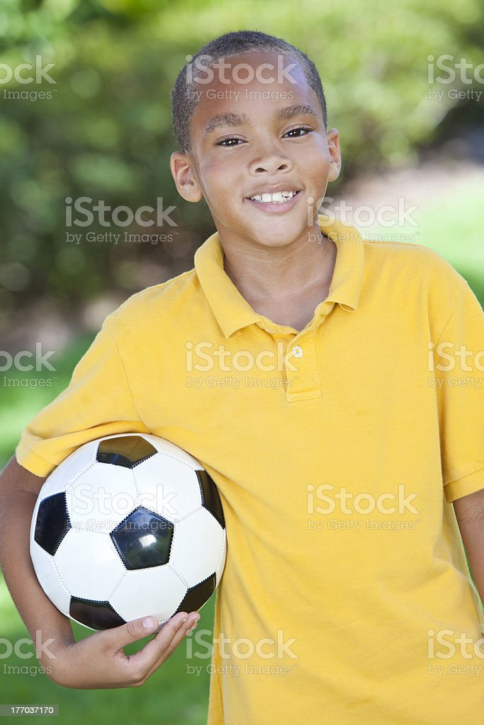 African American Boy Child Playing With Football or Soccer Ball royalty-free stock photo